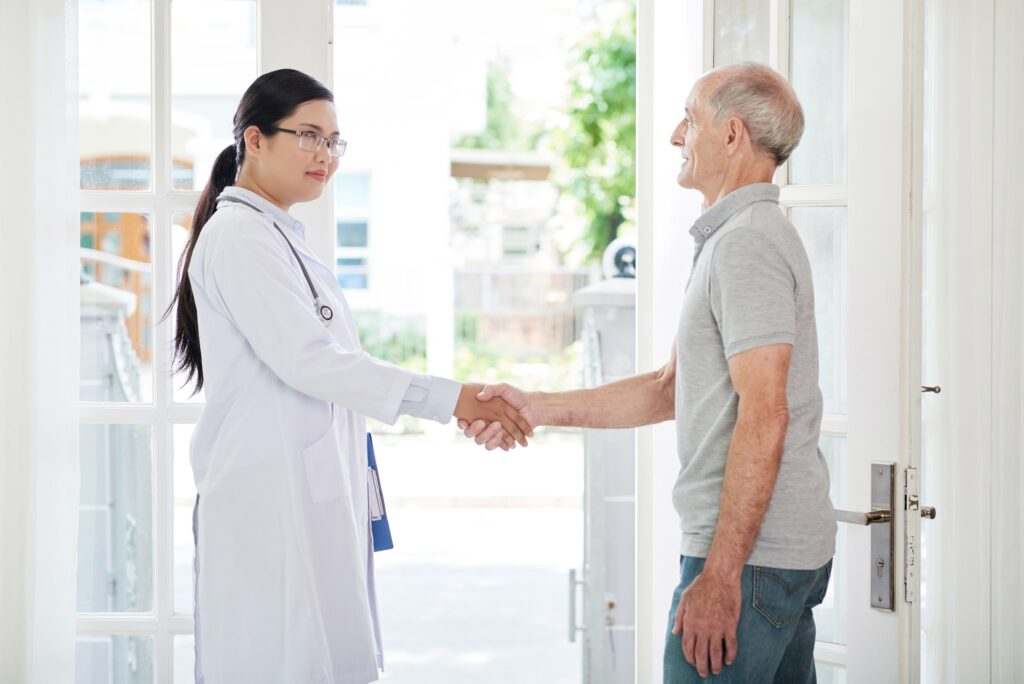 Senior patient shaking hand of doctor at home